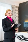 31529824-Housekeeping-manager-or-assistant-controlling-hotel-room-or-suit-with-checklist-on-tidiness--Stock-Photo