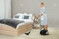 39433968-Female-Housekeeper-Cleaning-Rug-With-Vacuum-Cleaner-In-Hotel-Room-Stock-Photo